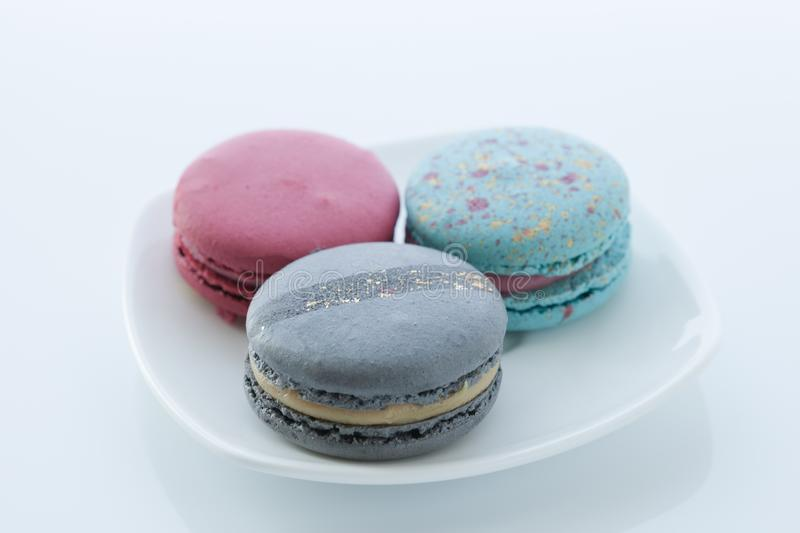 Assortment of different colored macaroons lies in a saucer with a top view stock photos