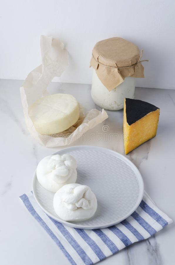 Assortment of different kinds of cheese:burrata,ricotta,gouda,provolone on marble table against white background.Vertical photo stock photo