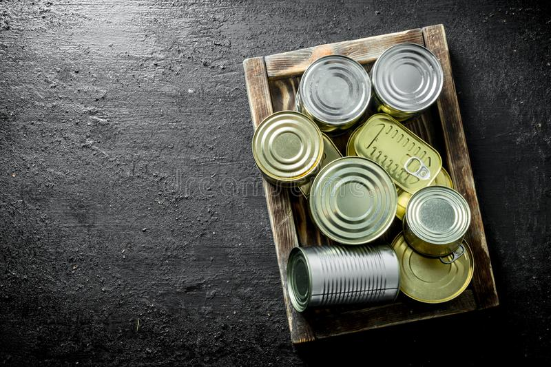 Assortment of different kinds of tin cans with canned food on tray. On black rustic background stock photography