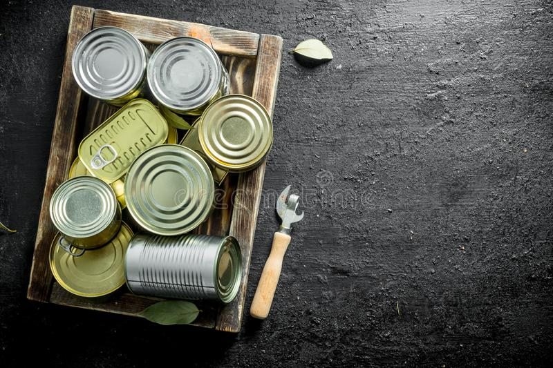 Assortment of different kinds of tin cans with canned food on tray. On black rustic background stock photo
