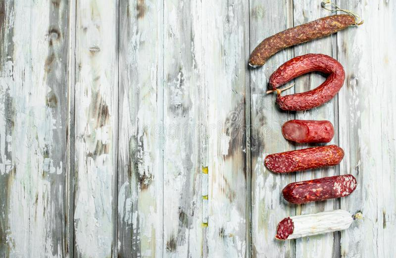 Assortment of different smoked salami with herbs and seasonings royalty free stock photos