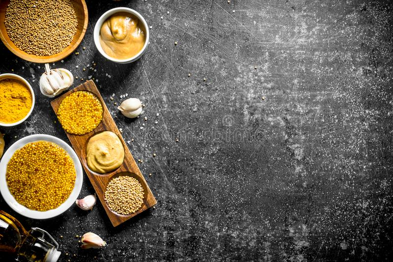 Assortment of different types of mustard in the bowl and on the stand. On dark rustic background stock photos