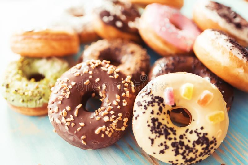 Assortment of donuts on a table. Assortment of donuts on a blue wooden table stock photo