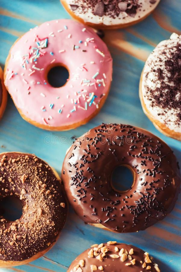 Assortment of donuts on a table. Assortment of donuts on a blue wooden table stock image
