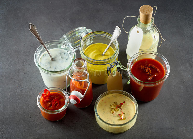 Assortment of dressings, sauces and condiments. With chili, ketchup, catsup, mustard, oil and mayonnaise , in various containers viewed from above in a catering stock photography