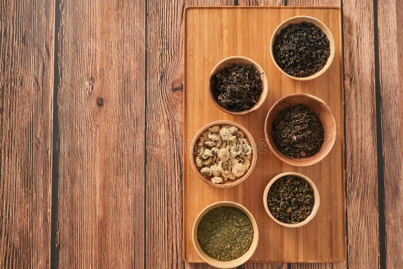 Assortment of dry tea in white bowls on wooden surface royalty free stock image