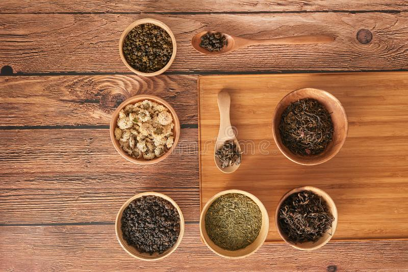 Assortment of dry tea in white bowls on wooden surface royalty free stock photos