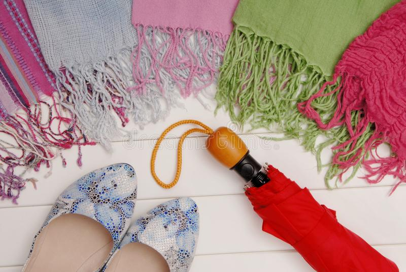 Assortment of female accessories, scarfs, red umbrella and blue stock photos