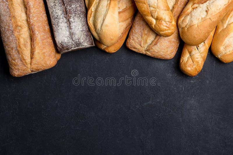 Assortment of fresh bread on dark background royalty free stock photo