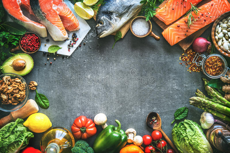 Assortment of fresh fish with aromatic herbs, spices and vegetables stock image