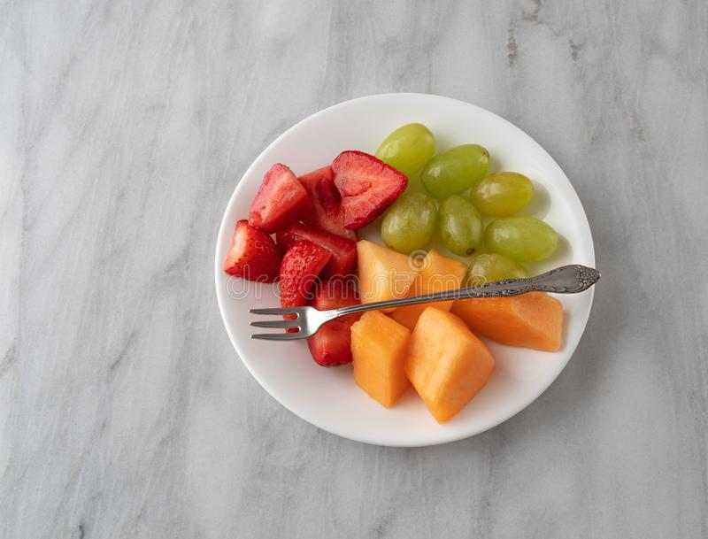 Assortment of fresh fruit with a fork on a white plate royalty free stock photo