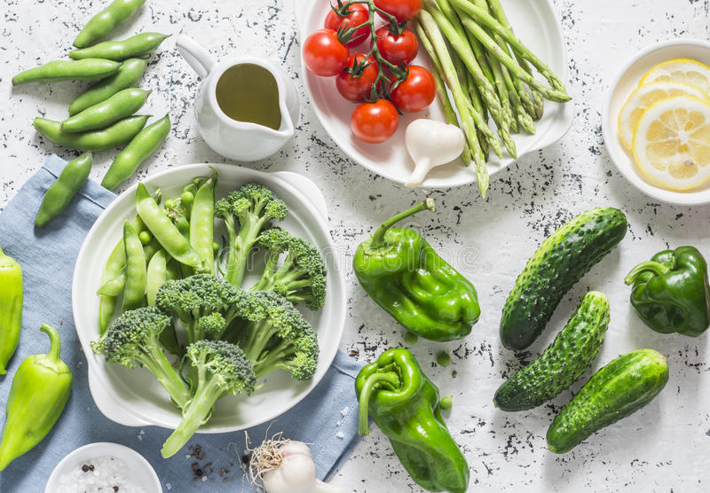 Assortment of fresh garden vegetables - asparagus, broccoli, beans, peppers, tomatoes, cucumbers, garlic, green peas on a light ba. Ckground, top view stock photo