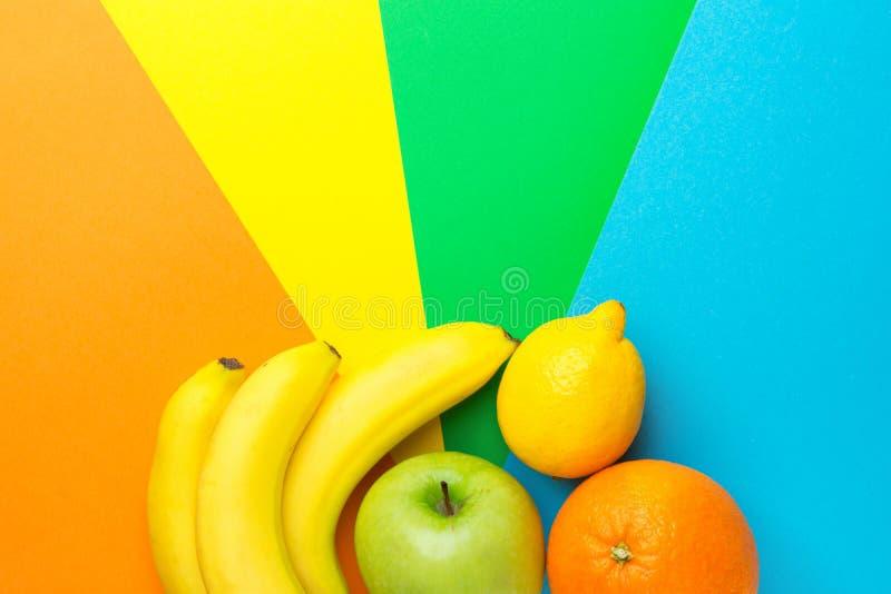 Assortment of fresh raw ripe fruits bananas apple orange lemon on multicolored pinwheel background. Creative food poster. Vitamins. Healthy lifestyle plant base royalty free stock photography