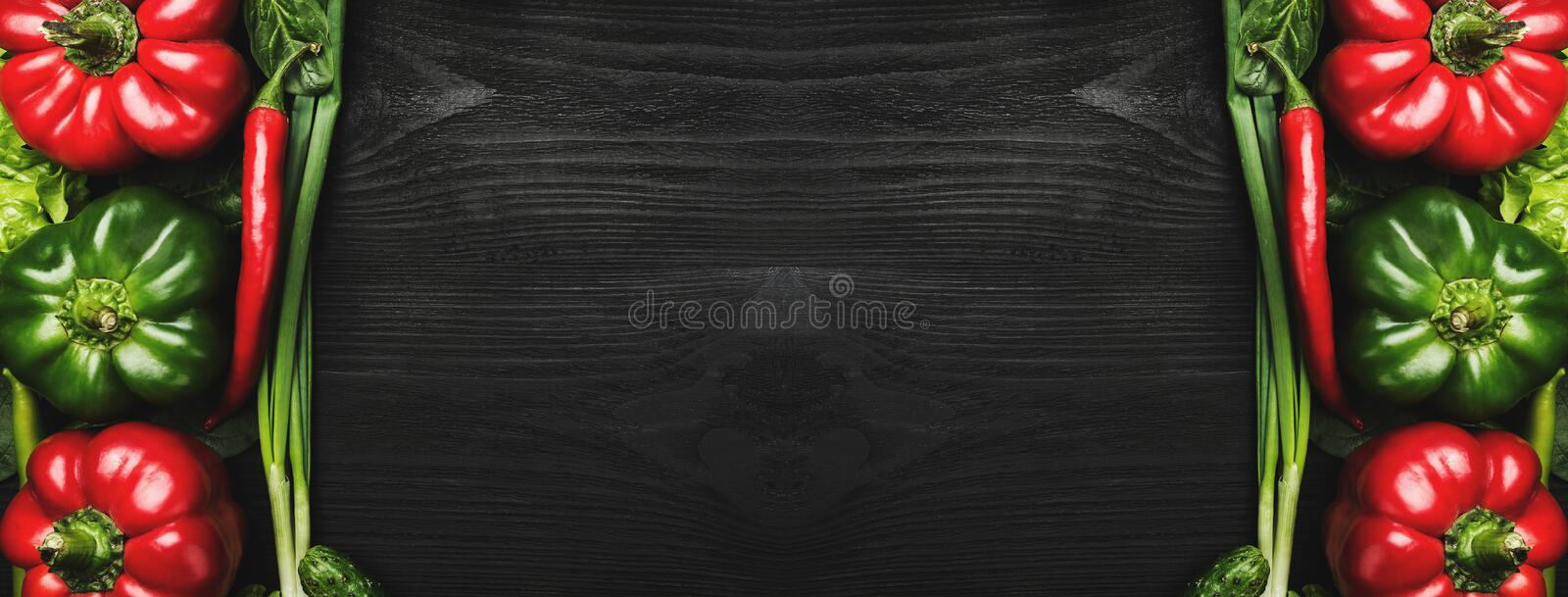 Assortment of fresh vegetables arranged in the frame shape on black wooden background, with space for text stock images