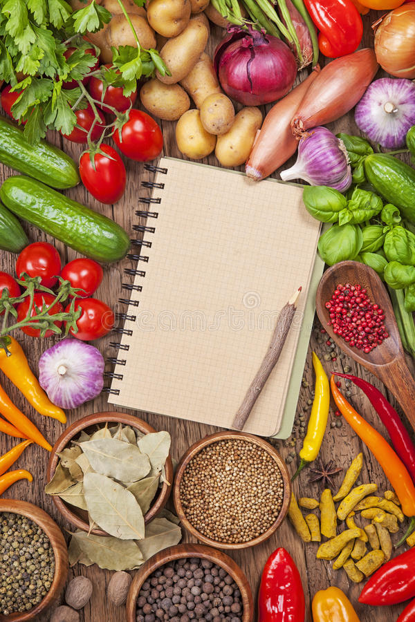 Fresh vegetables and blank recipe book. Assortment of fresh vegetables and blank recipe book on a wooden background stock photo