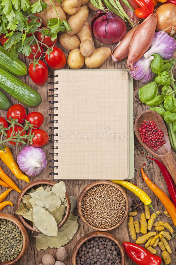 Assortment of fresh vegetables. And blank recipe book on a wooden background stock image