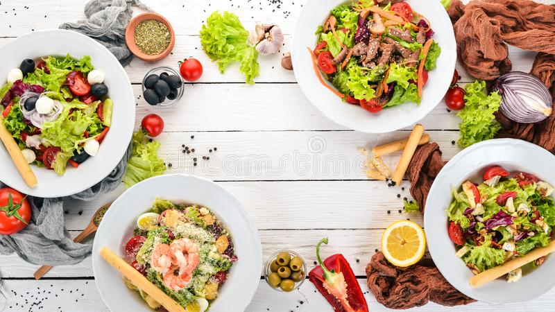 Assortment of fresh vegetables salads. Healthy food. On a white wooden background. stock photo