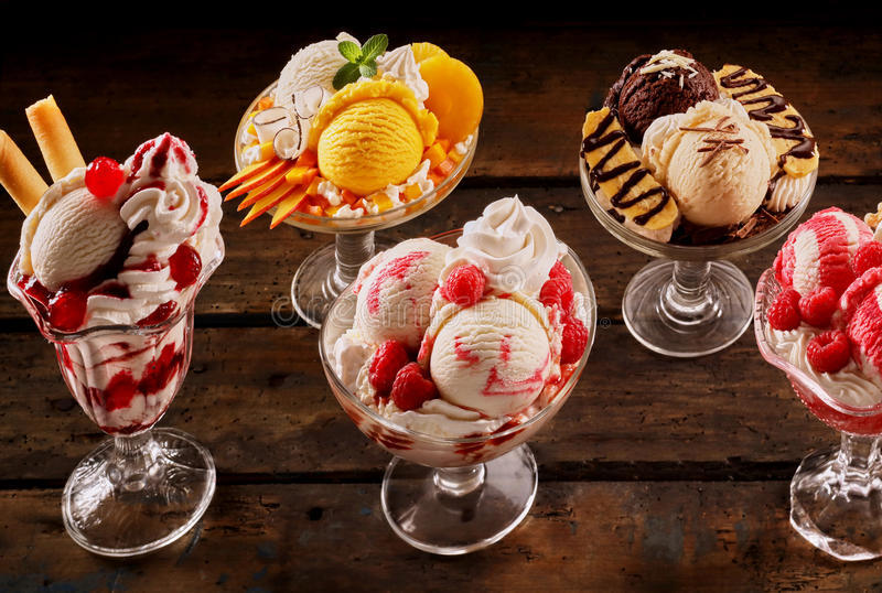 Assortment of fruity ice-cream sundae desserts. Made of artisanal Italian gelato garnished with cream and fresh, strawberries, raspberries, mango, pineapple royalty free stock photography