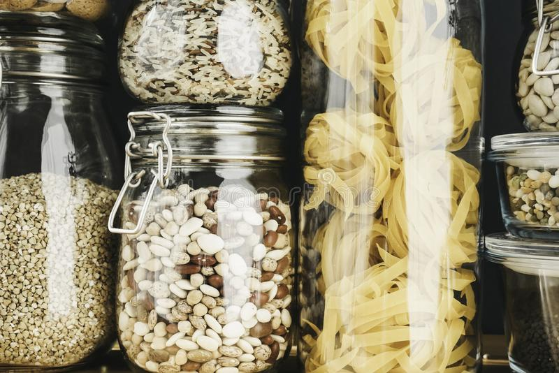 Assortment of grain products and pasta in glass storage containers on wooden table. Healthy cooking, clean eating, zero. Waste concept. Balanced dieting food royalty free stock image