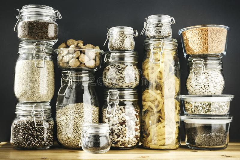 Assortment of grain products and pasta in glass storage containers on wooden table. Healthy cooking, clean eating, zero. Waste concept. Balanced dieting food royalty free stock photography