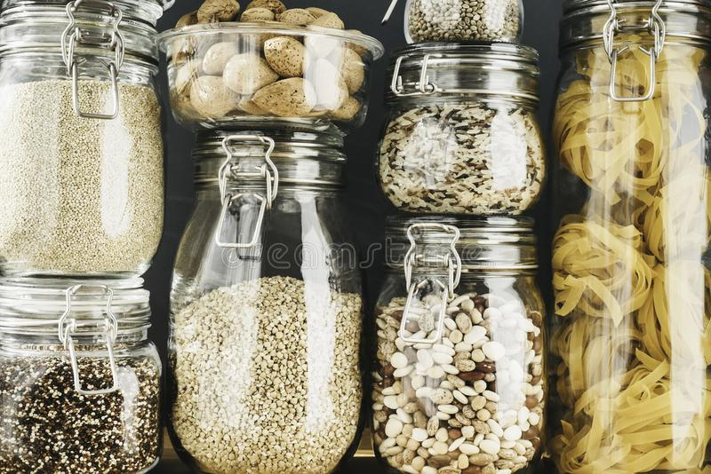 Assortment of grain products and pasta in glass storage containers on wooden table. Healthy cooking, clean eating, zero. Waste concept. Balanced dieting food royalty free stock images