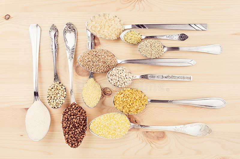 Assortment groats in spoons on soft beige wood board. Healthy food background. Assortment groats in spoons on soft beige wood board. Healthy food background royalty free stock images