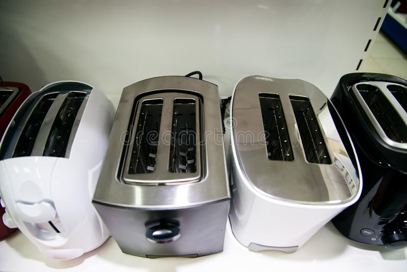 New toasters on the shelf in the store. Assortment of a kitchen fashionable modern beautiful stylish appliances at household store stock photos