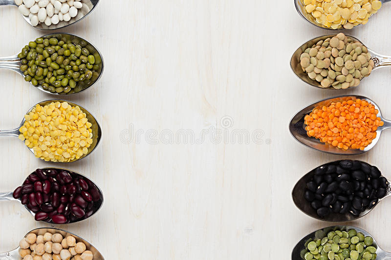 Assortment legume beans in spoons with copy space on white wood background. Top view, closeup royalty free stock photo