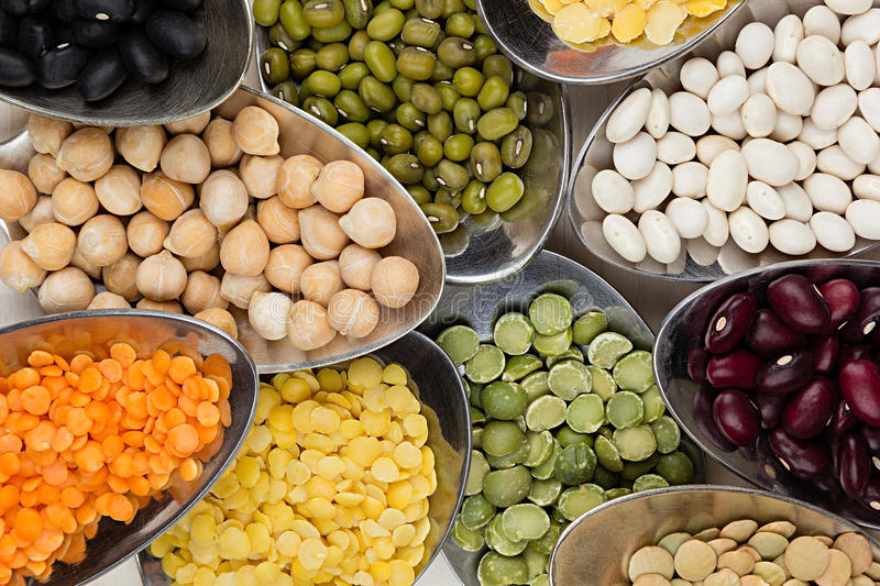 Assortment legume beans in spoons macro on white wood background. Top view, closeup royalty free stock images