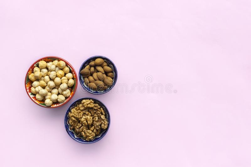 Assortment  mix of nuts, hazelnuts, almonds, walnuts in bowls on pink background. Flat lay, top view, copy space royalty free stock photos