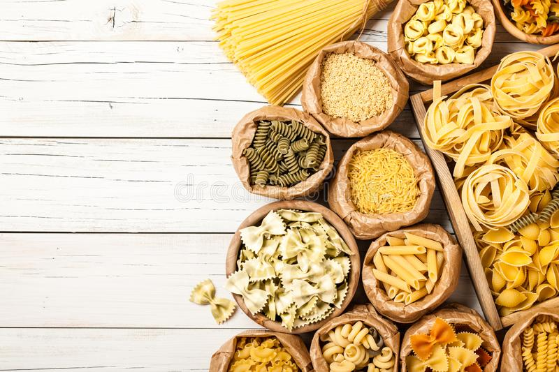 Assortment of pasta on a wooden table. Copy space stock images
