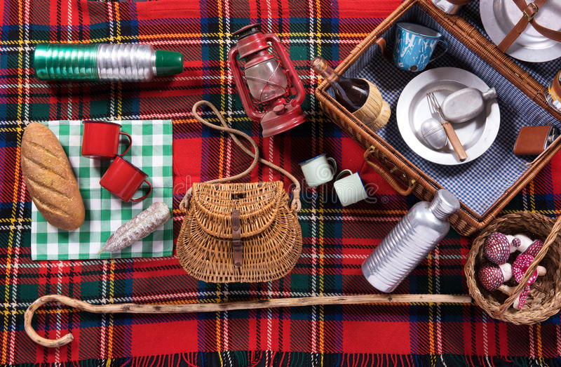 Assortment of picnic tools on a tartan rug. With an open hamper with wine and plates, wicker basket, bread, mugs, hurricane lamp crook and flask viewed from royalty free stock photography