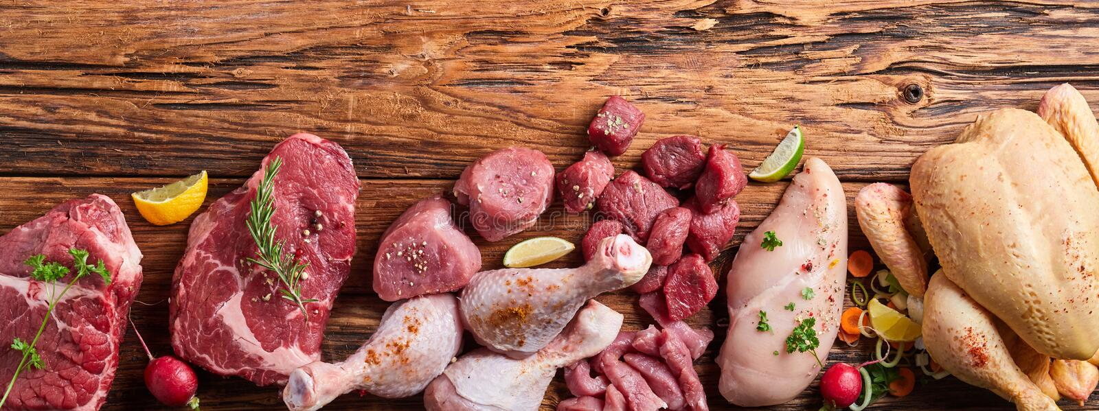 Assortment of raw meat on wooden table. With vegetables, greens and sprinkled with spices, viewed from above with copy space royalty free stock photos