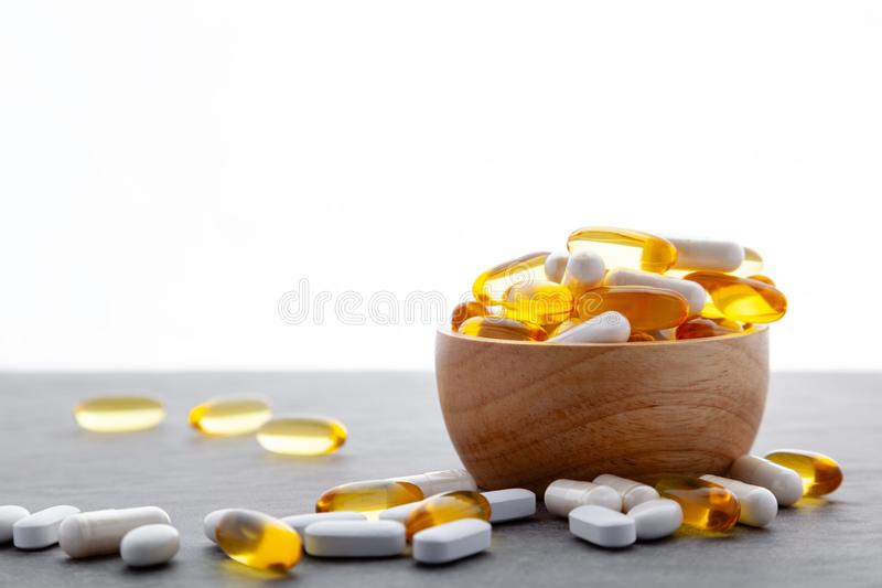 Assortment scattered pharmaceutical medicine tablets, pills, drugs in wooden bowl on gray background. White food dietary. Supplement hard shelled capsules royalty free stock photos