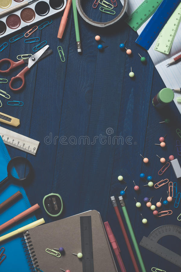 Assortment of school stationery such as paper clips, pins, notebook, pens, pencils, rulers, scissors lying on table with space to stock photography