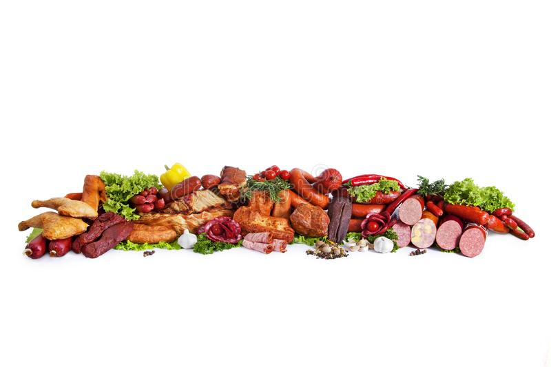 Assortment of smoked products. Decorated with vegetables and leaves of green salad. Isolated on white background royalty free stock photography