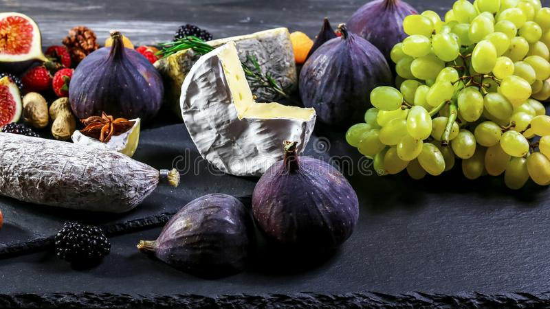 Assortment of snacks with cheese and sausage fruits and grape on old wooden table. top view. copy space stock photos