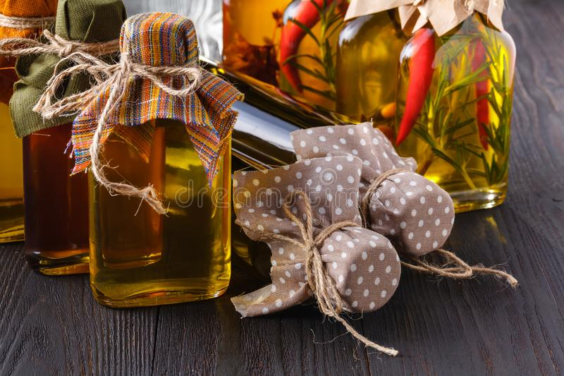 Assortment of spicy oils with herbs and spices in different bottles stock photo