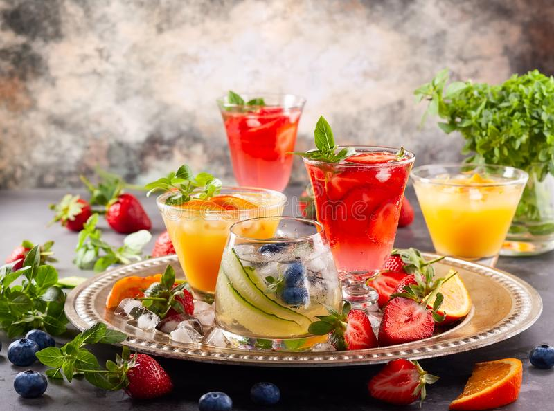 Assortment summer non-alcoholic cocktails. With fresh berries, herbs and fruits on dark background royalty free stock images