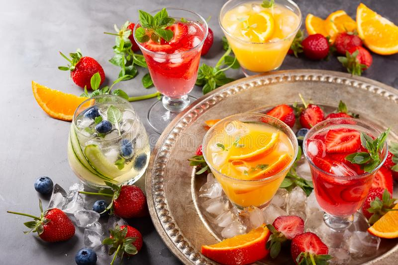 Assortment summer non-alcoholic cocktails. With fresh berries, herbs and fruits on dark background royalty free stock photos