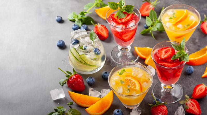 Assortment summer non-alcoholic cocktails. With fresh berries, herbs and fruits on dark background stock image