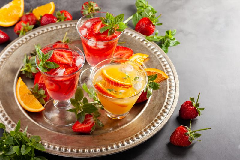 Assortment summer non-alcoholic cocktails. With fresh berries, herbs and fruits on dark background stock images