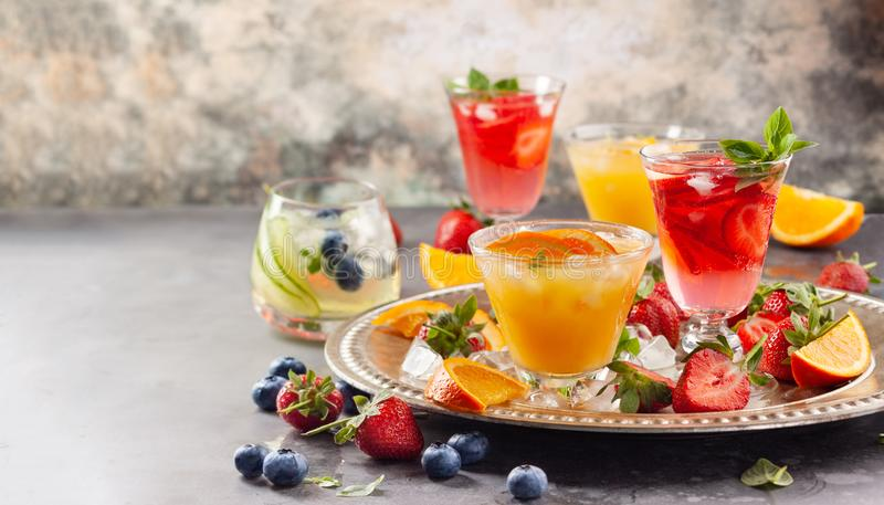 Assortment summer non-alcoholic cocktails. With fresh berries, herbs and fruits on dark background stock photos