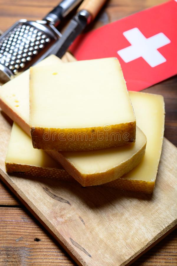 Assortment of Swiss cheeses Emmental or Emmentaler medium-hard cheese with round holes, Gruyere, appenzeller and raclette used for. Traditional cheese fondue royalty free stock image