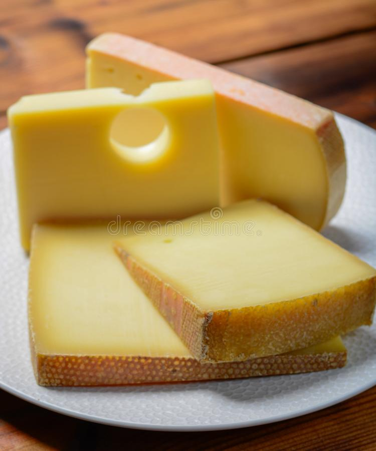 Assortment of Swiss cheeses Emmental or Emmentaler medium-hard cheese with round holes, Gruyere, appenzeller and raclette used for. Traditional cheese fondue or stock images