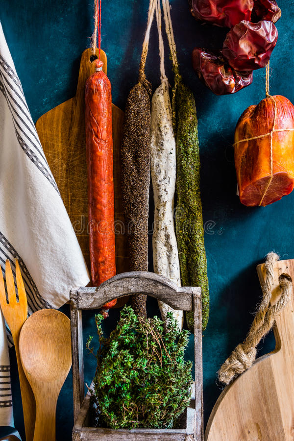 Assortment of traditional Spanish charcuterie meat sausages, fresh herbs thyme, kitchen utensils, towel, wood cutting board stock image