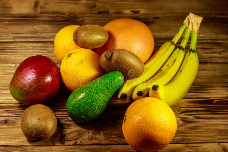 Assortment of tropical fruits on wooden table. Still life with bananas, mango, oranges, avocado, grapefruit and kiwi fruits stock photo