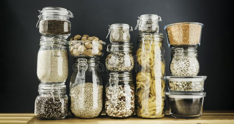 Assortment of uncooked grains, cereals and pasta in glass jars on wooden table. Healthy cooking, clean eating, zero stock photo