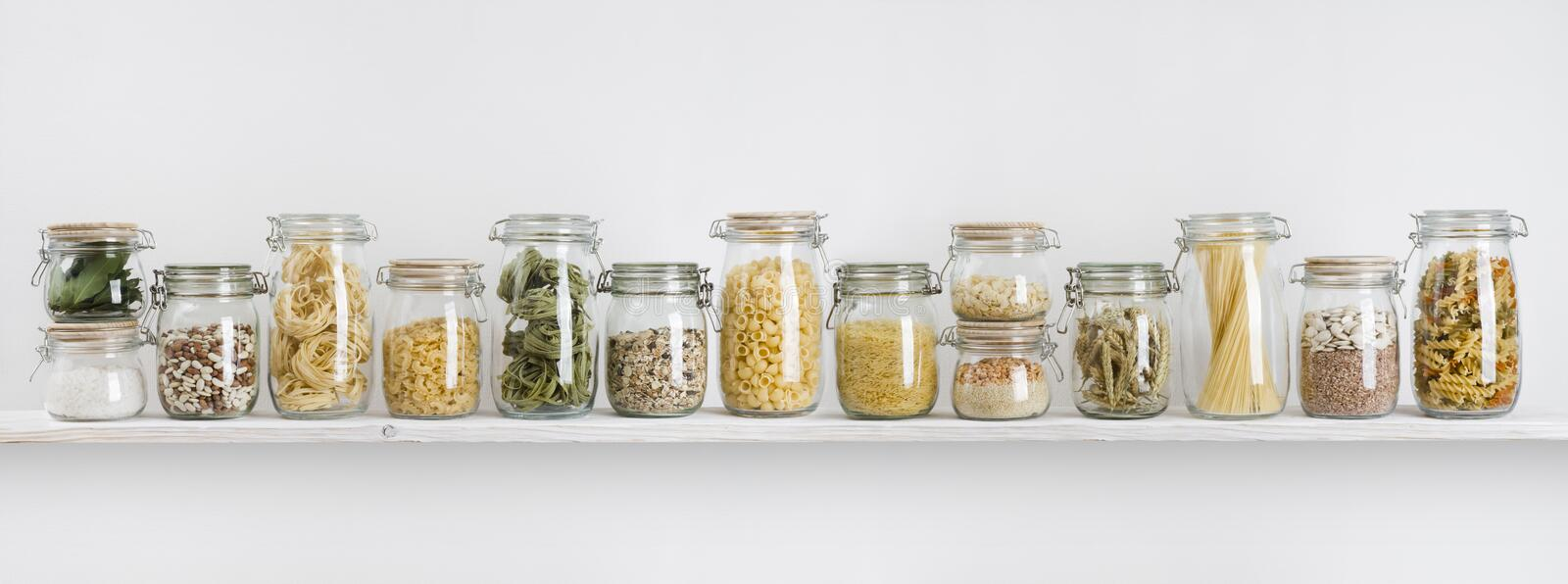 Assortment of uncooked groceries in glass jars arranged on shelf stock image