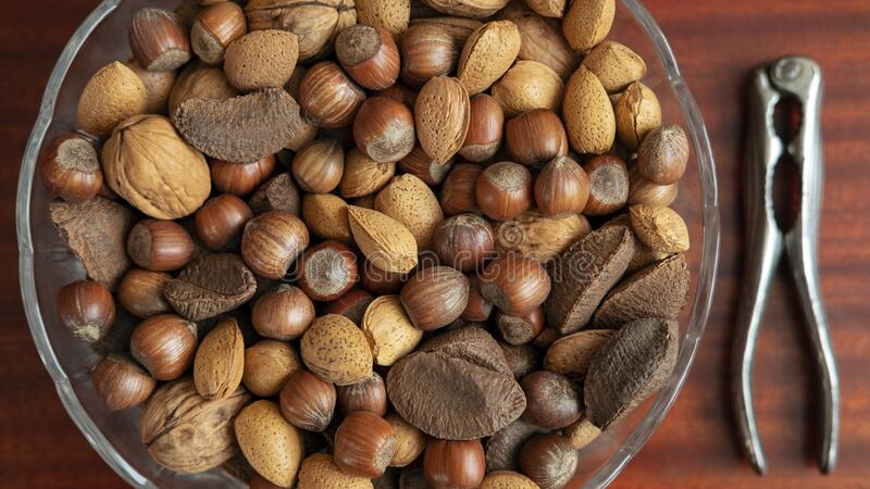Assortment of whole nuts, walnuts, almonds, hazelnuts and Brazil nuts in a bowl with a nut cracker on a side. Nutritious snack cracked and eaten in autumn or stock photo